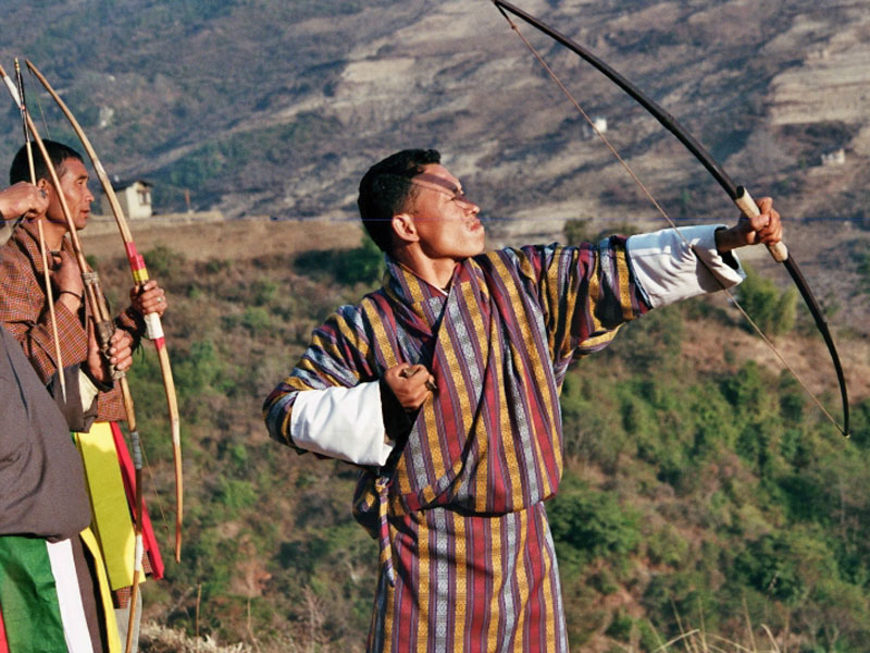 Bhutanese men in gho during a traditional archery match